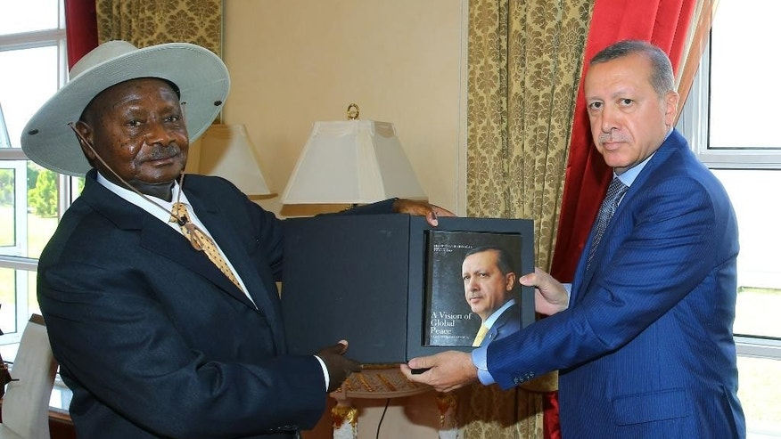 "Uganda's long-time president Yoweri Museveni, left, receives a book written by Turkey's President Recep Tayyip Erdogan, "" A Vision of Global Peace "" during a ceremony in the capital Kampala, Uganda, Wednesday, June 1, 2016. Museveni was sworn in in May for a fifth term taking him into his fourth decade in power, amid arrests of opposition politicians and a shutdown of social media. Erdogan is on a two-day state visit.(Kayhan Ozer, Presidential Press Service/Pool via AP)"