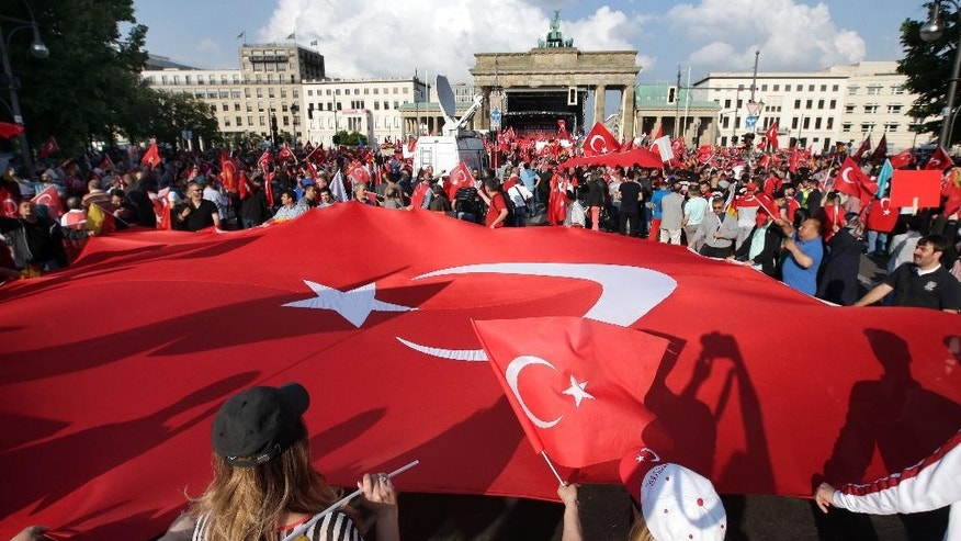 Protesters hold a giant flag of Turkey in front of the Brandenburg gate in Berlin, Germany, Wednesday, June 1, 2016, as they demonstrate against a resolution of the German federal parliament, Bundestag, on the Armenian Genocide a century ago. Turkey's relations with Germany will be harmed if the parliament in Berlin votes to describe the killings of Armenians last century as genocide, the Turkish prime minister said Wednesday. (AP Photo/Michael Sohn)