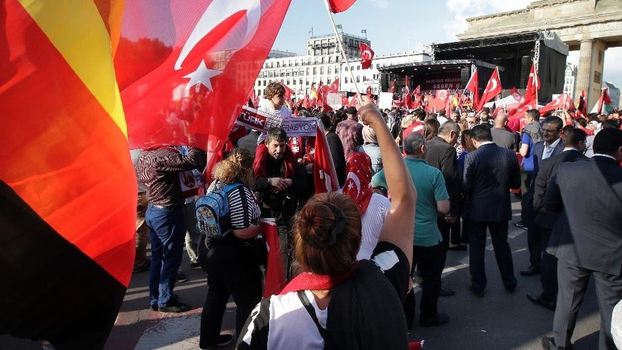 Protesters wave flags of Turkey and Germany in front of the Brandenburg gate in Berlin, Germany, Wednesday, June 1, 2016, as they demonstrate against a resolution of the German federal parliament, Bundestag, on the Armenian Genocide a century ago. Turkey's relations with Germany will be harmed if the parliament in Berlin votes to describe the killings of Armenians last century as genocide, the Turkish prime minister said Wednesday. (AP Photo/Michael Sohn)