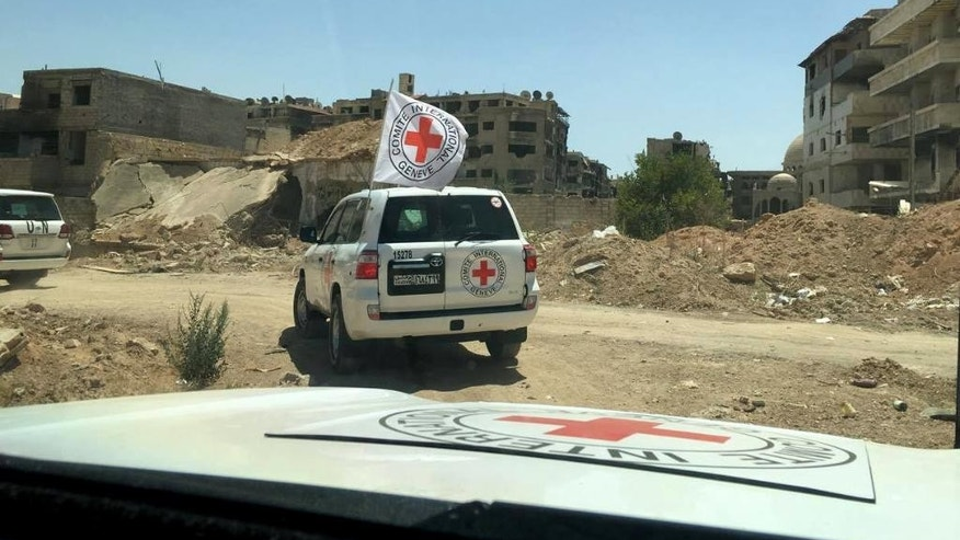 This image released by the International Committee for the Red Cross shows the first humanitarian aid convoy in Daraya, Syria on Wednesday, June 1, 2016. A besieged suburb of Syria's capital received humanitarian aid Wednesday for the first time since 2012, as the United Nations. The International Committee for the Red Cross (ICRC) reported that a joint convoy with the U.N. and the Syrian Arab Red Crescent entered the Damascus suburb of Daraya in the afternoon. The U.N. estimates that 4,000 to 8,000 people currently live in the suburb.(ICRC via AP)