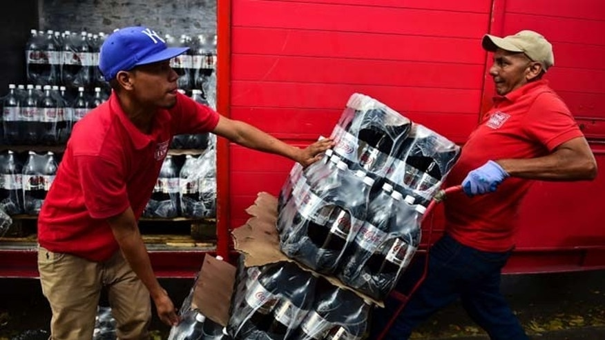 Workers unload bottles of Coca Cola from a truck in Caracas on May 27, 2016. Coca Cola suspended much of its distribution in Venezuela due to a shortage of sugar. / AFP / RONALDO SCHEMIDT        (Photo credit should read RONALDO SCHEMIDT/AFP/Getty Images)