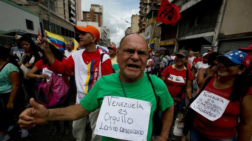 "A supporter of Venezuela's President Nicolas Maduro wears a sign that reads in Spanish ""Venezuela is Latin American pride"" and shouts slogans in support of Maduro at a rally in Caracas, Venezuela, Wednesday, June 1, 2016. Government supporters and state employees held a rally against ""foreign intervention"" in Venezuela's affairs. (AP Photo/Fernando Llano)"