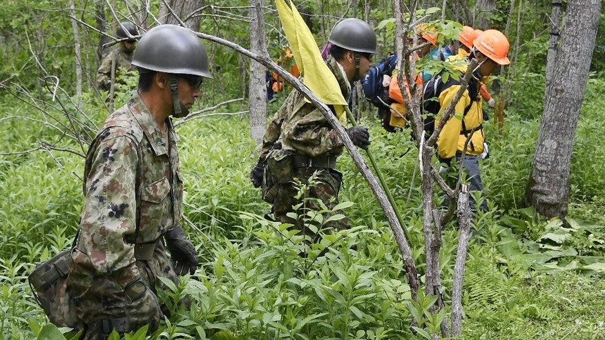 Members of the Ground Self-Defense Force conduct a search operation for Yamato Tanooka, a seven-year-old boy who has been missing since May 28, in a forest at Nanae town, in Japan's northernmost main island of Hokkaido Thursday, June 2, 2016. The search for the boy who disappeared after his parents left him behind in the Japanese forest as punishment pushed into a sixth day on Thursday, but with no clues to his fate. (Daisuke Suzuki/Kyodo News via AP) JAPAN OUT, CREIT MANDATORY