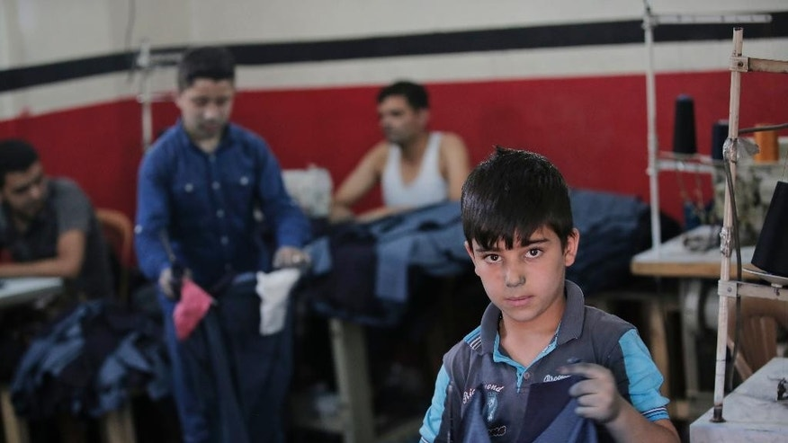 In this Thursday, June 2, 2016 photo, Mohammed, 10, a Syrian refugee child from Aleppo, works with other Syrians at a clothes workshop in Gaziantep, southeastern Turkey. Mohammed, whose father was killed in Syria, works 10-hours a day for about 100 Turkish Liras a week, (some 38 US dollars / 30 euros) to support him and his mother living now in Turkey. Turkey is hosting 3 million refugees and is expected to receive more, although the human rights group Amnesty International on Friday, June 3, 2016, urged the European Union to stop plans to return asylum-seekers to Turkey. (AP Photo/Lefteris Pitarakis)