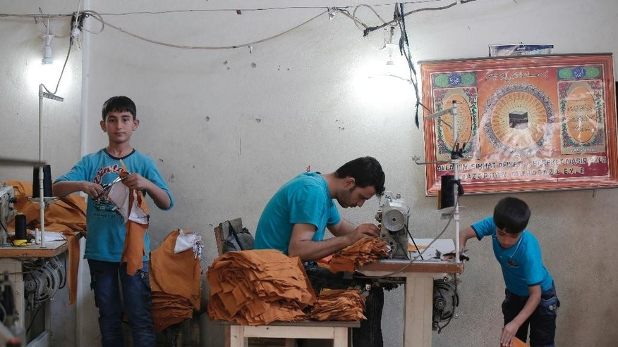 "In this Thursday, June 2, 2016 photo, Syrian refugees, including children, work at a clothes workshop in Gaziantep, southeastern Turkey.  Turkey is currently hosting some 3 million refugees, and is expected to receive more but Amnesty International on Friday, June 6, 2016, has urged the European Union to stop plans to return asylum-seekers to Turkey, saying the EU-Turkey deal to curb irregular migration was ""illegal"" and ""reckless"". (AP Photo/Lefteris Pitarakis)"