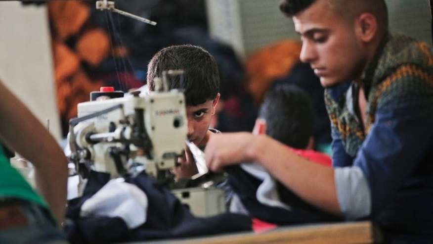 In this Thursday, June 2, 2016 photo, Issa, 10, left, a Syrian refugee child from Aleppo, works with other Syrians at a clothing workshop in Gaziantep, southeastern Turkey. Issa, works 10-hours per day for about 100 Turkish Liras a week, (some 38 US dollars / 30 euros) to support him and his family. Turkey is currently hosting some 3 million refugees, and is expected to receive more but Amnesty International on Friday, June 3, 2016, has urged the European Union to stop plans to return asylum-seekers to Turkey. (AP Photo/Lefteris Pitarakis)