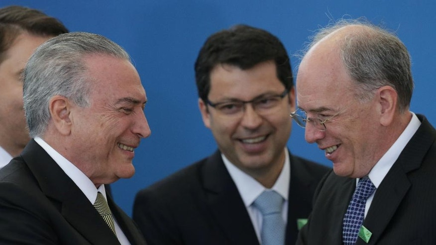 Brazil's acting President Michel Temer, left, greets the new president of state oil company Petrobras, Pedro Parente, as the new president of the Bank of Brazil, Paulo Rogerio Caffarelli, center, looks on during their inauguration ceremony at Planalto presidential palace in Brasilia, Brazil, Wednesday, June 1, 2016. (AP Photo/Eraldo Peres)