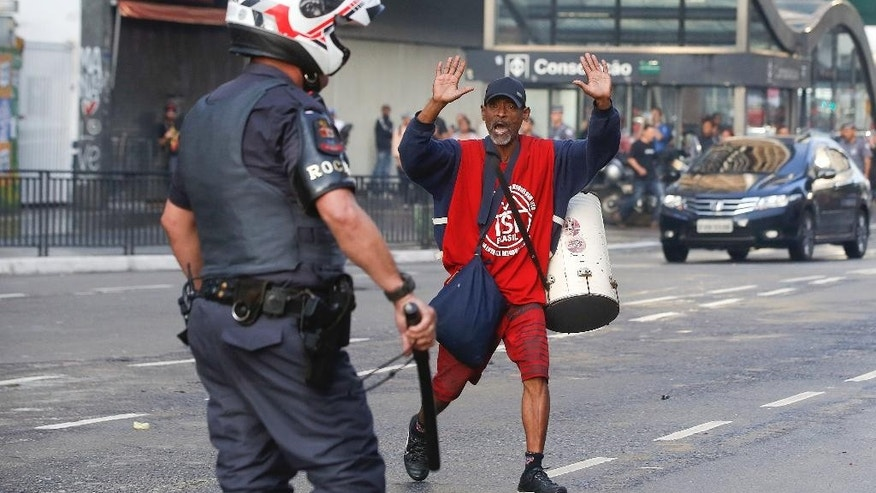 A demonstrator of the Homeless Workers Movement shouts at a police officer that they to stop firing tear gas during a protest, in Sao Paulo, Brazil, Wednesday, June 1, 2016. The movement organized the protest against acting President Michel Temer and in support of suspended President Dilma Rousseff.  (AP Photo/Andre Penner)