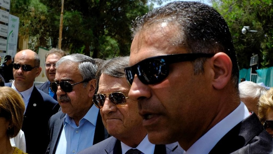Cyprus' President Nicos Anasatsiades, center right, and Turkish Cypriot leader Mustafa Akinci, center left, before joining Greek and Turkish Cypriot children at Ledras palace crossing point in divided capital Nicosia in east Mediterranean island of Cyprus, Thursday, June, 2, 2016. Anastasiades and Akinci met with 100 fifth-grade Greek and Turkish Cypriot students - 50 from either community - to underscore their commitment to reaching an accord that will reunify the island. (AP Photo/Petros Karadjias)