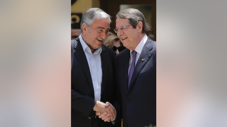 Cyprus' President Nicos Anasatsiades, right, and Turkish Cypriot leader Mustafa Akinci shake hands before joining Greek and Turkish Cypriot children inside the UN controlled buffer zone at Ledras palace crossing point in divided capital Nicosia in east Mediterranean island of Cyprus, Thursday, June, 2, 2016. Anastasiades and Akinci met with 100 fifth-grade Greek and Turkish Cypriot students - 50 from either community - to underscore their commitment to reaching an accord that will reunify the island. (AP Photo/Petros Karadjias)