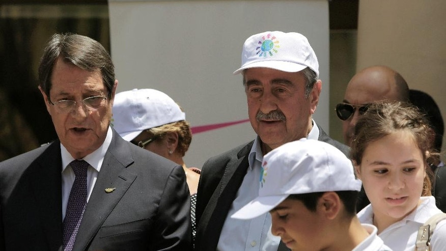 Cyprus' President Nicos Anasatsiades, left, and Turkish Cypriot leader Mustafa Akinci stand with Greek and Turkish Cypriots children, inside the UN controlled buffer zone at Ledras palace crossing point in divided capital Nicosia in east Mediterranean island of Cyprus, Thursday, June, 2, 2016. Anastasiades and Akinci met with 100 fifth-grade Greek and Turkish Cypriot students - 50 from either community - to underscore their commitment to reaching an accord that will reunify the island. (AP Photo/Petros Karadjias)