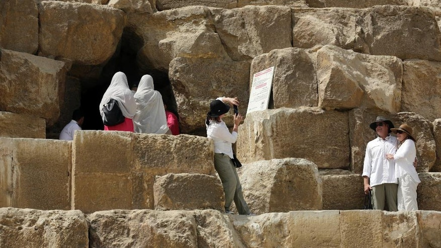 Tourists pose for pictures at the entrance of the Great Pyramid, built by Cheops, known locally as Khufu in Giza, Egypt, Thursday, June 2, 2016. A scientific team scanning the Great Pyramid aimed at discovering the famed pharaonic monument's secrets including possible hidden burial chambers. (AP Photo/Amr Nabil)