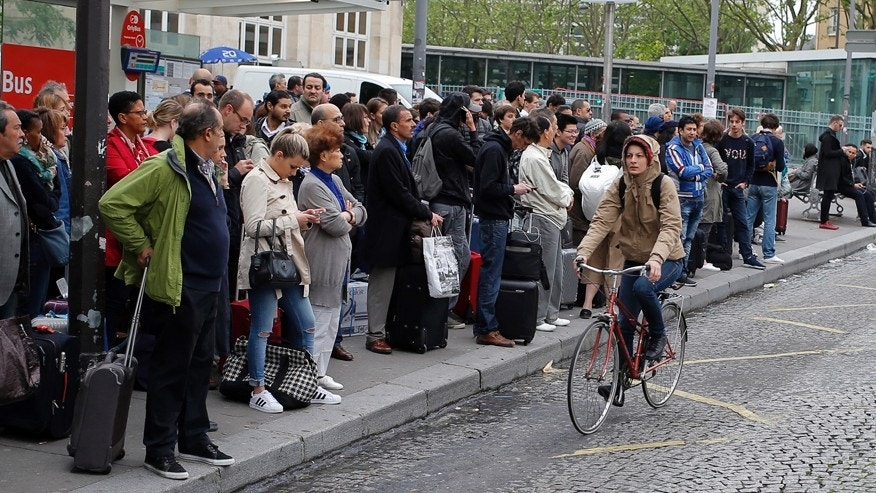 June 2, 2016: A woman rides a bicycle next to commuters waiting for a bus to Orly Airport during a railway strike in Paris.
