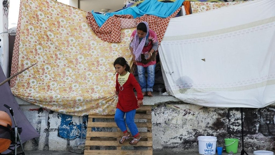 An Afghan girl get out her makeshift tent at the old international airport, which is used as a shelter for over 3,500 refugees and migrants, in southern Athens on Monday, May 30, 2016.  The government has been moving migrants from makeshift camps into organized shelters and the Greek government said Monday they will continue to clear the Greek- Macedonian border area over the next few days. (AP Photo/Petros Giannakouris)