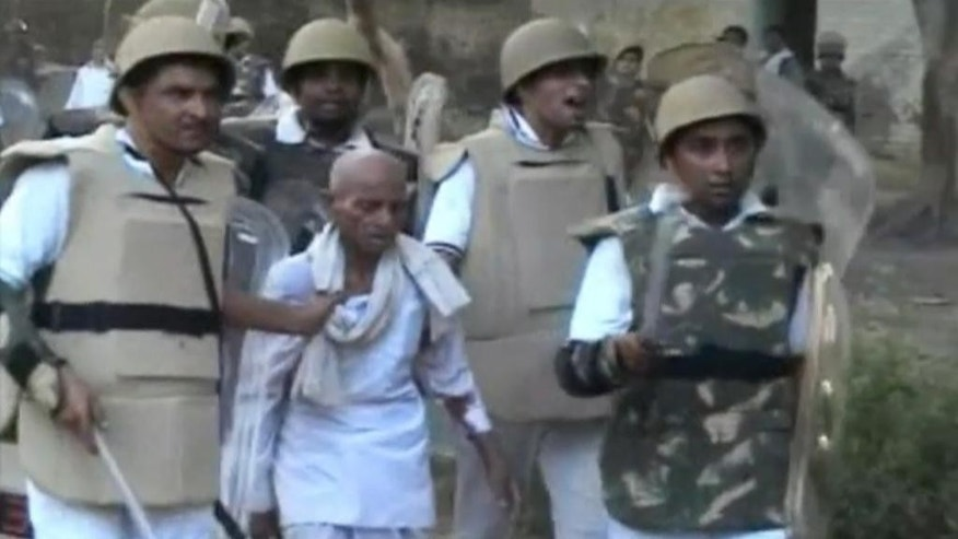 In this Thursday, June 2, 2016 image made from video, paramilitary soldiers detain an unidentified man from the site of violent clashes in Mathura, India. Police efforts to evict thousands of people squatting in a makeshift protest camp in the heart of a north Indian city ended in bloodshed as people opened fire from treetops and police retaliated, police said Friday, June 3, 2016. (AP Video via AP)