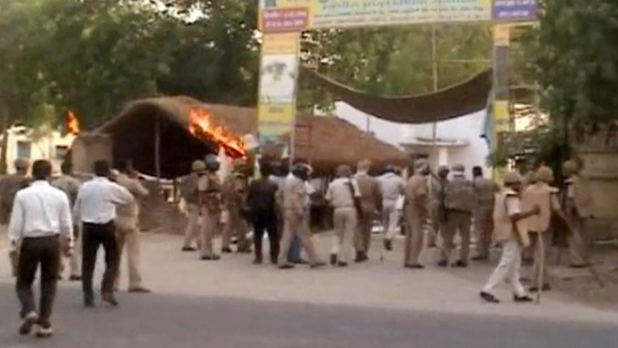 This Thursday, June 2, 2016 image made from video shows Indian policemen and paramilitary soldiers near the site of violent clashes in Mathura, India. Police efforts to evict thousands of people squatting in a makeshift protest camp in the heart of a north Indian city ended in bloodshed as people opened fire from treetops and police retaliated, police said Friday, June 3, 2016. (AP Video via AP)