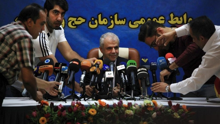 Journalists adjust their microphones ahead of a press conference held by head of Iran's Hajj and Pilgrimage Organization Saeed Ohadi, center, in Tehran, Iran, Thursday, June 2, 2016. Iran officially announced on Thursday that it won't be sending pilgrims to the hajj this year, blaming Saudi Arabia for the move and claiming the kingdom has failed to provide adequate security for the pilgrims. (AP Photo/Vahid Salemi)