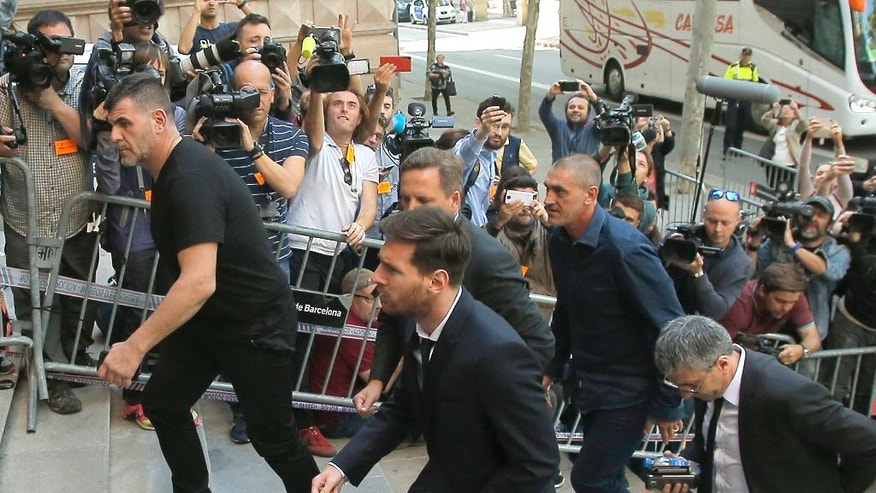 Barcelona soccer player Lionel Messi, center, arrives at a court in Barcelona, Spain, Thursday, June 2, 2016. Messi's tax trial began Tuesday. Messi and his father, Jorge Horacio, have been charged with three counts of tax fraud. They could be sentenced to nearly two years in prison if found guilty of defrauding Spain's tax authority of 4.1 million euros ($4.5 million) from 2007-09. (AP Photo/Manu Fernandez)