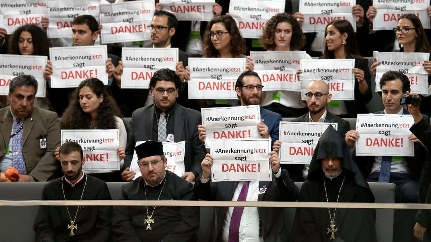 "Guests hold posters of the 'recognition now' organization reading ""RecognitionNow says Thank you"" during a meeting of the German Federal Parliament, Bundestag,  in Berlin, Germany, Thursday, June 2, 2016. The German Parliament is to vote Thursday on whether to label the killings of Armenians by Ottoman Turks a century ago as genocide. (AP Photo/Michael Sohn)"