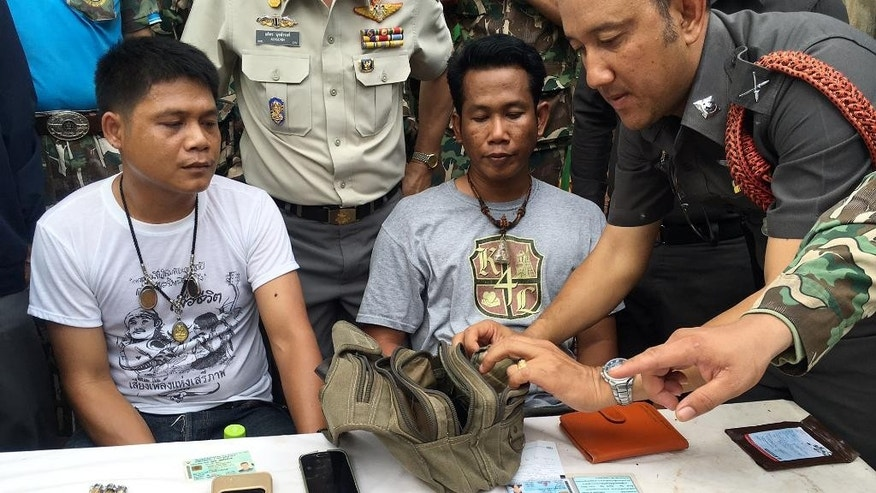 "A police officer, right, examines the belongings of two men arrested after attempting to remove tiger skin's and products from the ""Tiger Temple,"" in Saiyok district in Kanchanaburi province, west of Bangkok, Thailand, Thursday, June 2, 2016. Thai police say they stopped a truck carrying two tiger skins and other animal parts as it was leaving the temple, two staff members were arrested and charged with possession of illegal wildlife. (AP Photo) THAILAND OUT"