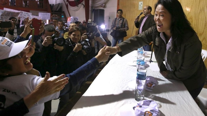 Fuerza Popular presidential candidate Keiko Fujimori greets supporters as she arrives at a campaign rally in Lima, Peru, Thursday, June 2, 2016. The South American country is gearing up for a tight June 5th runoff between Keiko Fujimori, the daughter of jailed former President Alberto Fujimori, and former World Bank economist Pedro Pablo Kuczynski. (AP Photo/Martin Mejia)