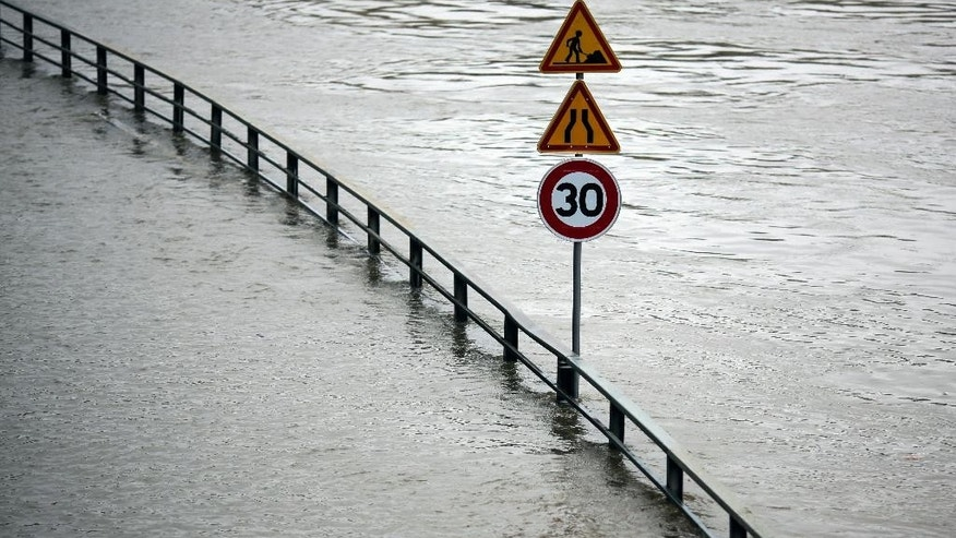 A street sign stands in the water on a flooded street by the river Seine in Paris, Wednesday, June 1, 2016. Paris City Hall closed roads along the shore of the Seine from the southwest edge of the city to the neighborhood around the Eiffel Tower as the water level has risen 4.3 meters (14 feet 1 inches) higher than usual. (AP Photo/Markus Schreiber)