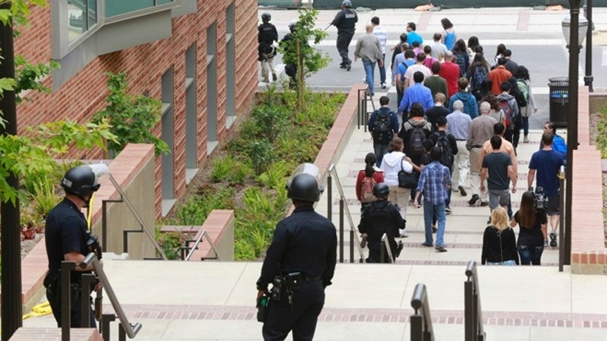 Los Angeles Police officers escort people at the UCLA campus after a fatal shooting at the University of California, Los Angeles, Wednesday, June 1, 2016, in Los Angeles. Los Angeles police chief says shooting at UCLA was murder-suicide. (AP Photo/Damian Dovarganes)