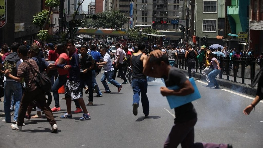 People take cover from tear gas fired by Bolivarian National Police during a protest demanding food, a few blocks from Miraflores presidential palace in Caracas, Venezuela, Thursday, June 2, 2016. Venezuela is seeing rising frustration with widespread food shortages and triple-digit inflation. (AP Photo/Fernando Llano)