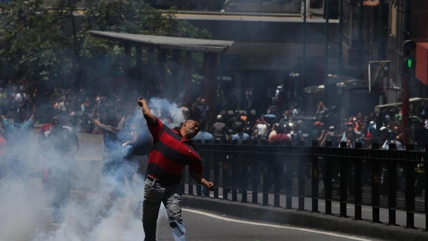 A man throws tear gas back at Bolivarian National Police as clashes break out during a protest demanding food, a few blocks from Miraflores presidential palace in Caracas, Venezuela, Thursday, June 2, 2016. Venezuela is seeing rising frustration with widespread food shortages and triple-digit inflation. (AP Photo/Fernando Llano)