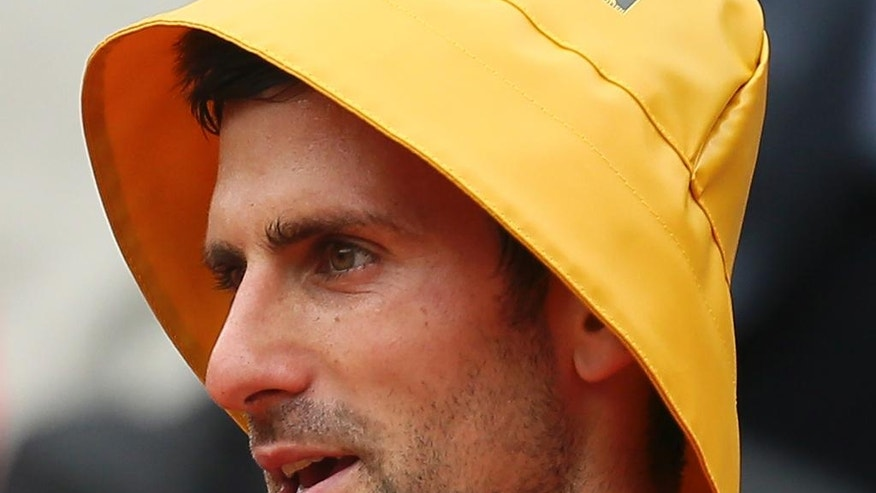 Serbia's Novak Djokovic wears a rain cap he took from a TV journalists after winning his fourth round match of the French Open tennis tournament against Spain's Roberto Bautista Agut at the Roland Garros stadium in Paris, France, Wednesday, June 1, 2016. (AP Photo/David Vincent)
