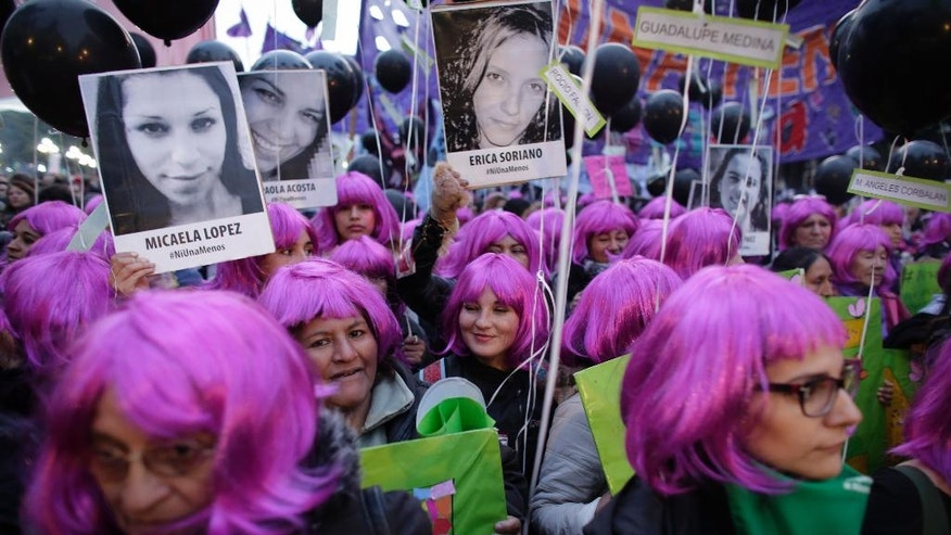 "Demonstrators holding photos of victims of gender violence march outside the National Congress in Buenos Aires, Argentina, Friday, June 3, 2016. Thousands marched under the Spanish slogan #niunamenos, which in English means ""not even one less."" Women's rights group Casa del Encuentro reports 275 femicides or gender-based killing of women in the past year. (AP Photo/Victor R. Caivano)"