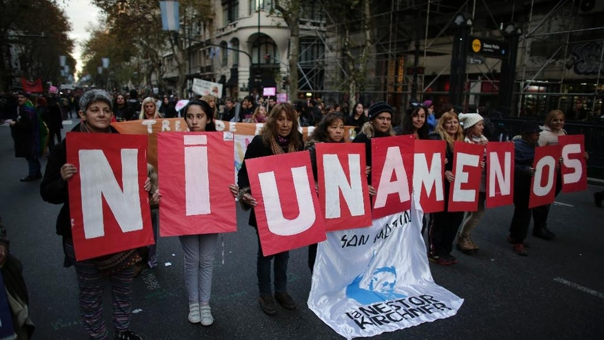"Demonstrators hold placards with a phrase that reads in English ""not even one less"" during a march against domestic violence outside the National Congress in Buenos Aires, Argentina, Friday, June 3, 2016. The women's rights group Casa del Encuentro reported 275 femicides or gender-based killing of women in the past year. (AP Photo/Victor R. Caivano)"