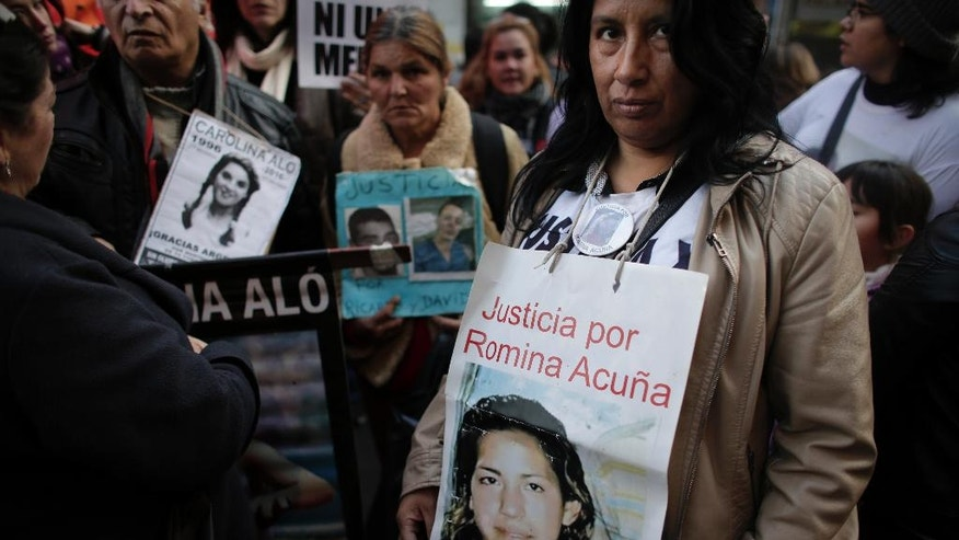 "Demonstrators, holding the photos of their relatives who were victims of gender violence, march outside the National Congress in Buenos Aires, Argentina, Friday, June 3, 2016. Thousands marched under the Spanish slogan #niunamenos, which in English means ""not even one less."" Women's rights group Casa del Encuentro reports 275 femicides or gender-based killing of women in the past year. (AP Photo/Victor R. Caivano)"