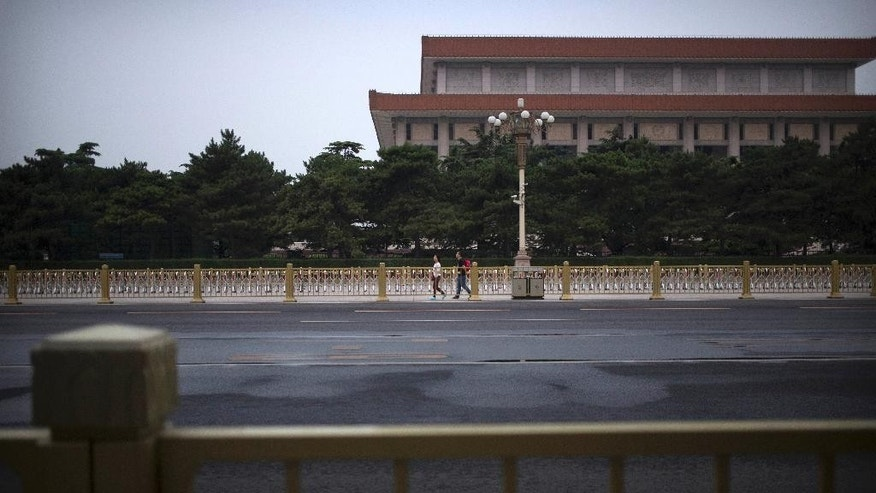 A pair of visitors walk near the Chairman Mao Memorial Hall at Tiananmen Square in Beijing, Saturday, June 4, 2016. Saturday marks the 27th anniversary of China's bloody crackdown on pro-democracy protests centered on Beijing's Tiananmen Square. (AP Photo/Mark Schiefelbein)