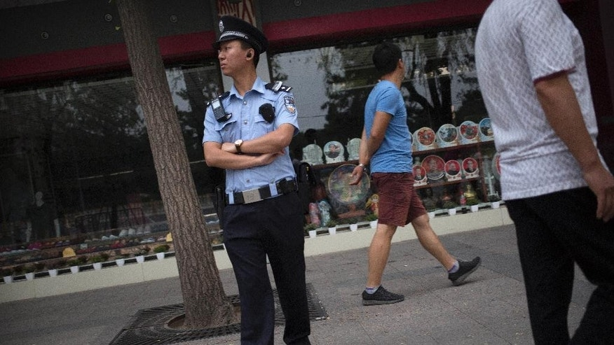 A police officer stands guard on the sidewalk of a street adjacent to Tiananmen Square in Beijing, Saturday, June 4, 2016. Saturday marks the 27th anniversary of China's bloody crackdown on pro-democracy protests centered on Beijing's Tiananmen Square. (AP Photo/Mark Schiefelbein)