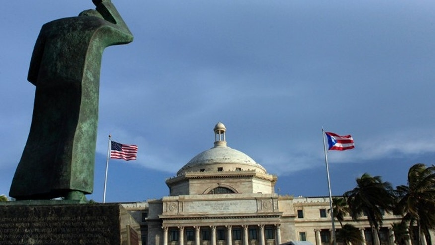 FILE - In this Wednesday, July 29, 2015, file photo, a bronze statue of San Juan Bautista stands in front of Puerto Ricos Capitol as U.S. and Puerto Rican flags fly in San Juan, Puerto Rico. After months of pleading from the government of Puerto Rico, the U.S. Congress agreed on Wednesday, May 18, 2016, to help the territory restructure its massive public debt. (AP Photo/Ricardo Arduengo, File)