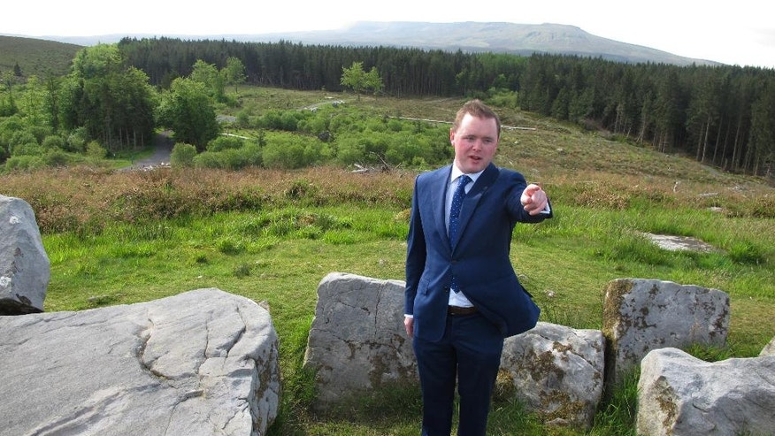 Blacklion-based county councilman John Paul Feeley stands amid the remains of a 4,500-year-old wedge tomb as he tells visitors about the region's major European-sponsored tourism initiative, the Global Geopark, atop Tullygobban Hill, Republic of Ireland, overlooking the border with Northern Ireland on Wednesday, May 25, 2016. Trails built with EU funds allow visitors to visit Neolithic tombs and other monuments dating back to 2500 B.C. (AP Photo/Shawn Pogatchnik)
