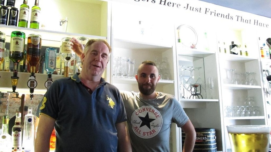 Paul Leonard, left, and his son Stephen pose behind the bar of their pub in Belcoo, Northern Ireland, on Wednesday, May 25, 2016. Paul Leonard says he'll probably vote to leave the EU in the June 23 referendum because he thinks the UK, including Northern Ireland, can do better economically outside the bloc, while Stephen plans to vote to stay. (AP Photo/Shawn Pogatchnik)