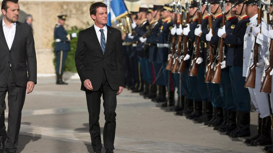 French Prime Minister Manuel Valls, center and Greek State Minister Nikos Papas, left review the Honor guard during a wreath laying ceremony at the tomb of the Unknown Soldier in central Athens on Thursday, June 2, 2016. Valls has arrived in Greece for a two-day visit expected to focus on economic cooperation, among tight security measures. (AP Photo/Petros Giannakouris)