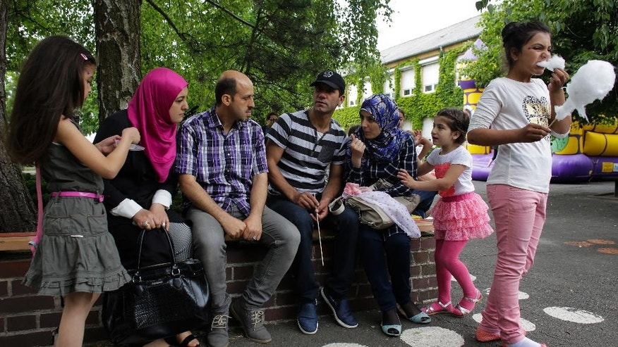 In this photo taken Friday, May 27, 2016, Syrian refugees Halima Taha, second from left, and her husband Fadi Sayed Ahmad, third from left, talk with another Syrian migrant family during the school festival of their children of the elementary school in the village Golzow, about 80 kilometers (50 miles) east of Berlin, Germany. When the elementary school in Golzow couldn't find the 15 students needed to set up a first-grade class, town officials persuaded two Syrian families to move to the small town on the Polish border. (AP Photo/Markus Schreiber)
