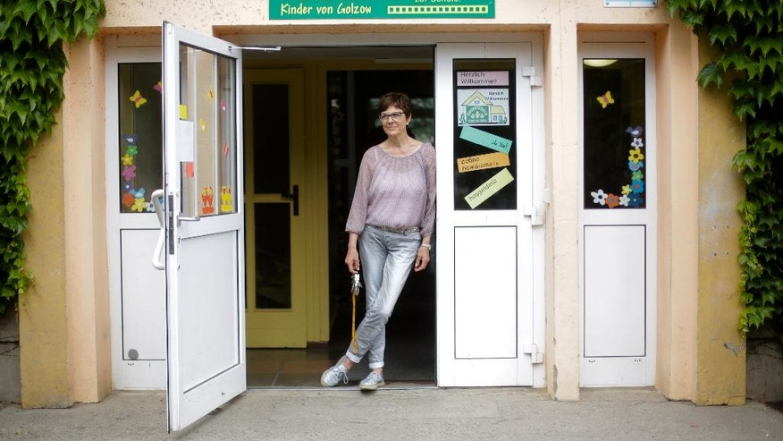 In this photo taken Friday, May 27, 2016, school director Gaby Thomas poses at the entrance of the elementary school in the village of Golzow, about 80 kilometers (50 miles) east of Berlin, Germany. When the elementary school in Golzow couldn't find the 15 students needed to set up a first-grade class, town officials persuaded two Syrian families to move to the small town on the Polish border. (AP Photo/Markus Schreiber)