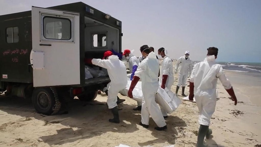 Emergency services remove the body of a victim as more than 100 bodies are pulled from the sea near the western city of Zwara, Libya, Friday June 3, 2016, after a smuggling boat carrying mainly African migrants sank into the Mediterranean.  Libya's navy spokesman Col. Ayoub Gassim says that the bodies of more than 100 migrants have been retrieved, but the death toll is likely to be higher. (APTV via AP) TV OUT