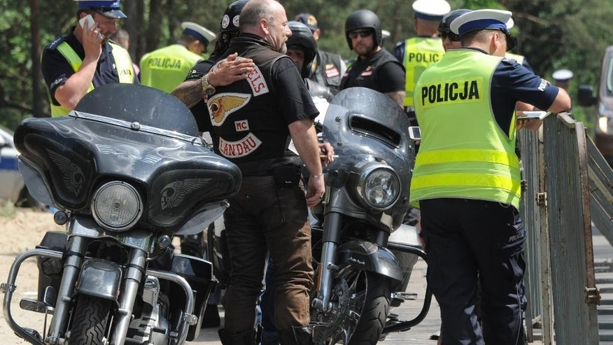 A group of Hells Angels bikers are checked by police officers as they wait to enter an enclosed holiday center in Rynia near Warsaw, Poland, Friday, June 3, 2016. Hundreds of Hells Angels bikers from across Europe and the U.S. came to Poland for their annual meeting. (AP Photo/Alik Keplicz)