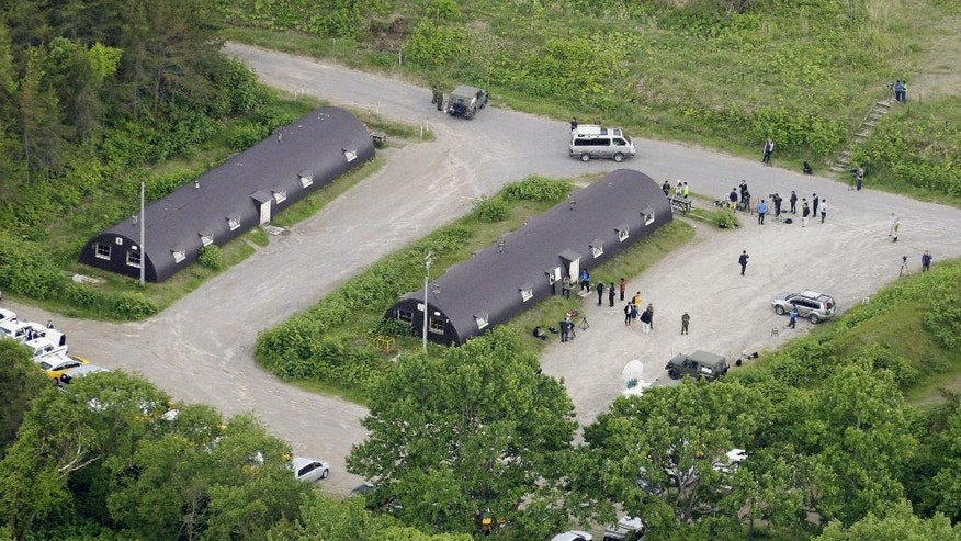 The media and members of the Self-Defence Forces stand near the building, right, where the 7-year-old Japanese boy who went missing nearly a week ago, was found, in a military drill area in Shikabe, on the northernmost main island of Hokkaido Friday, June 3, 2016. The boy, missing since Saturday, was found unharmed Friday, police said, in a case that had set off a nationwide debate about parental disciplining. (Takaki Yajima/Kyodo News via AP) JAPAN OUT, MANDATORY CREDIT