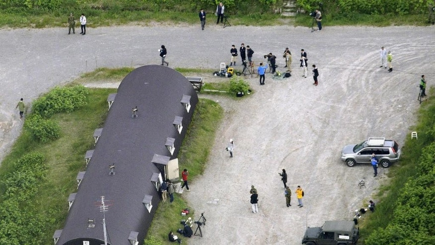 The media and members of the Self-Defence Forces stand near the building where the 7-year-old Japanese boy who went missing nearly a week ago, was found, in a military drill area in Shikabe, on the northernmost main island of Hokkaido Friday, June 3, 2016. The boy, missing since Saturday, was found unharmed Friday, police said, in a case that had set off a nationwide debate about parental disciplining. (Takaki Yajima/Kyodo News via AP) JAPAN OUT, MANDATORY CREDIT