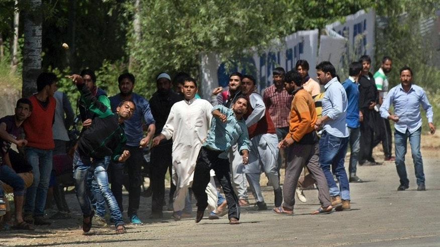 FILE - In this Friday, May 27, 2016, file photo, Kashmiri Muslim villagers throw stones at Indian security personnel in support of rebels during a gunbattle in Khonshipora, 40 kilometers (25 miles) west of Srinagar, Indian controlled Kashmir. Frustrated after decades of political stasis and military operations to root out rebels in their midst, Kashmiri villagers are rising up at the first sight of troops entering their village. The trend puts the disputed region's poor villagers in the center of India's fight against anti-India insurgents. (AP Photo/Dar Yasin, File)