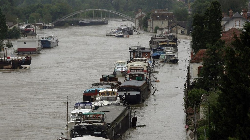 Boats are lined up on the flooded Loing Canal in St Mammes, where the Loing joins the Seine south of Paris, France Thursday June 2, 2016. Floods inundating parts of France and Germany have left five people dead and thousands trapped in homes or cars, as rivers have broken their banks from Paris to Bavaria.(AP Photo/Jerome Delay)