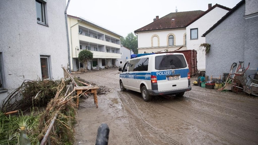 A police car patrols in a street of Simbach am Inn, southern Germany, Friday, June 3, 2016. Several people have been killed when flooding hit some places in Bavaria. (Peter Kneffel/dpa via AP)