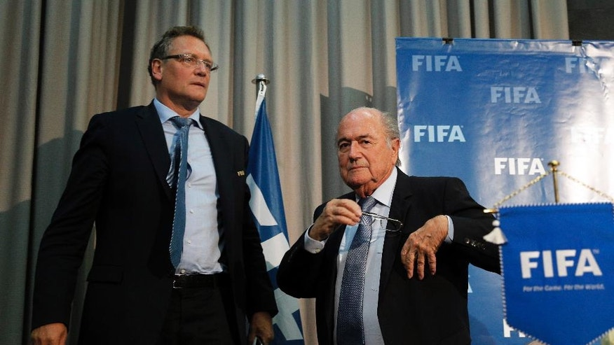 FILE - In this Friday, Dec. 19, 2014 file photo former FIFA president Sepp Blatter and former FIFA secretary general Jerome Valcke, left, leave a press conference in Marrakech, Morocco.  The Swiss attorney general's office confirms new raids on FIFA offices Friday June 3, 21016, in ongoing investigations of former FIFA president Sepp Blatter and former FIFA secretary general Valcke.  Blatter and Valcke both deny wrongdoing.  (AP Photo/Christophe Ena, FILE)