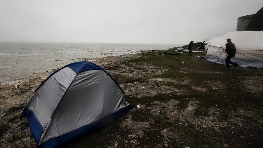Migrants set up in a new makeshift camp along the storm-hit cliffs near the port of Dieppe, northern France, Wednesday, June 1, 2016. A group of around 150 Albanian migrants are setting up a camp near the English channel, hoping to be able to cross the waterway into the UK.(AP Photo/Michel Spingler)